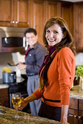 Mature woman drinking wine while husband cooks pasta